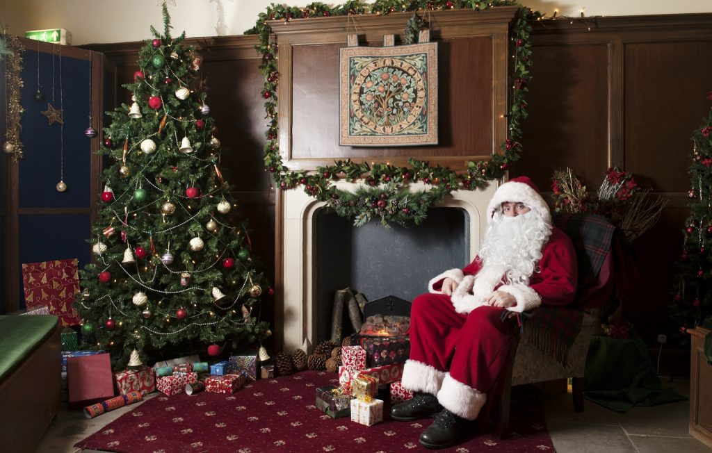 Father Christmas sitting in an armchair next to a fireplace and Christmas tree at Duff House