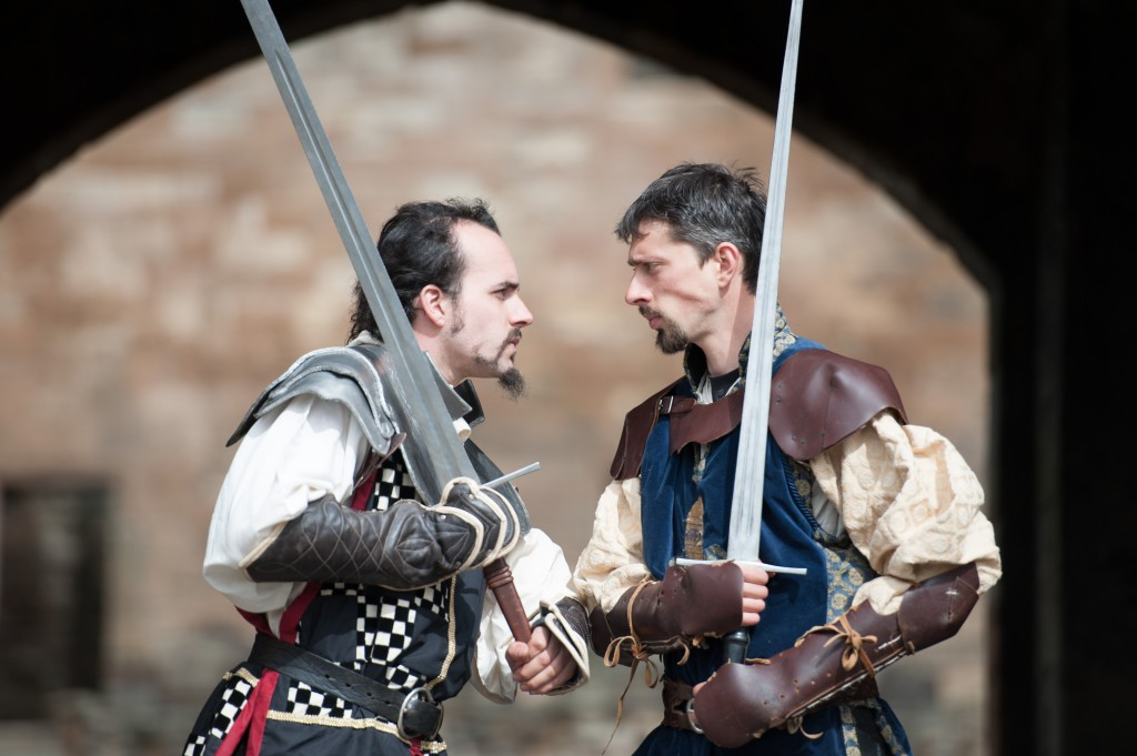 Two reenactors in knight uniforms and swords staring at each other, prepared to fight