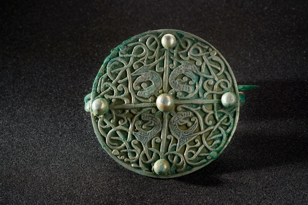 Openwork silver disc brooch on a black background