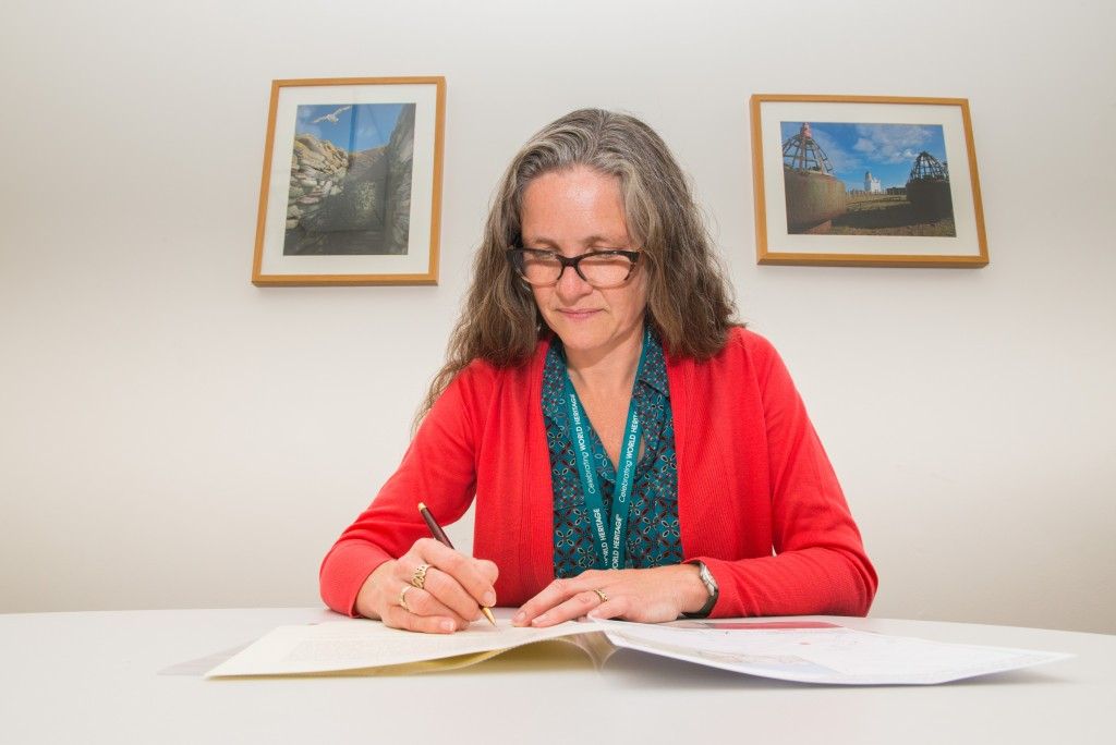 Director of Heritage Management, Barbara Cummins, signing a scheduling document in her office