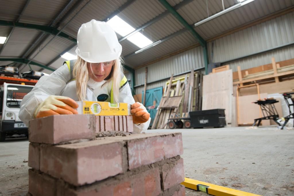 A woman measuring a brick