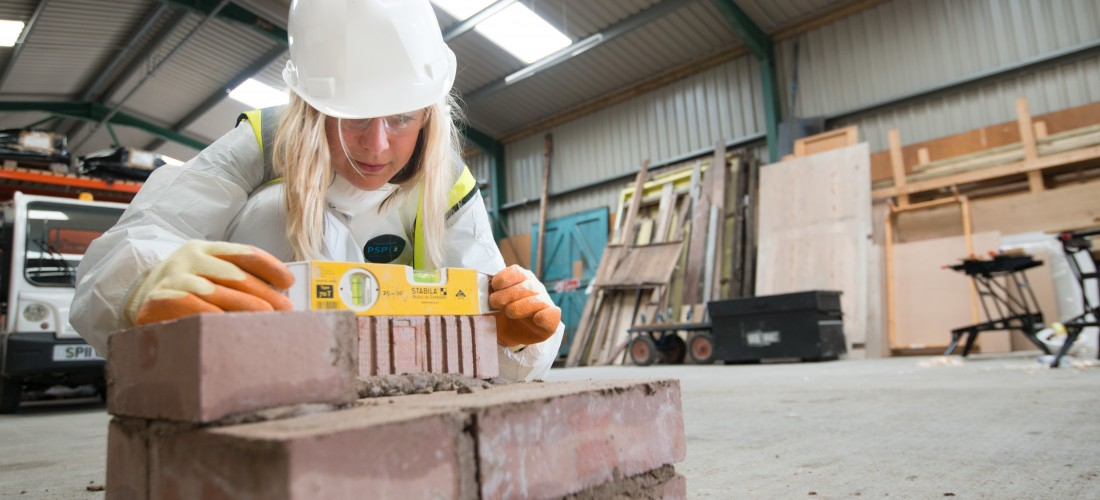 A woman measuring a brick