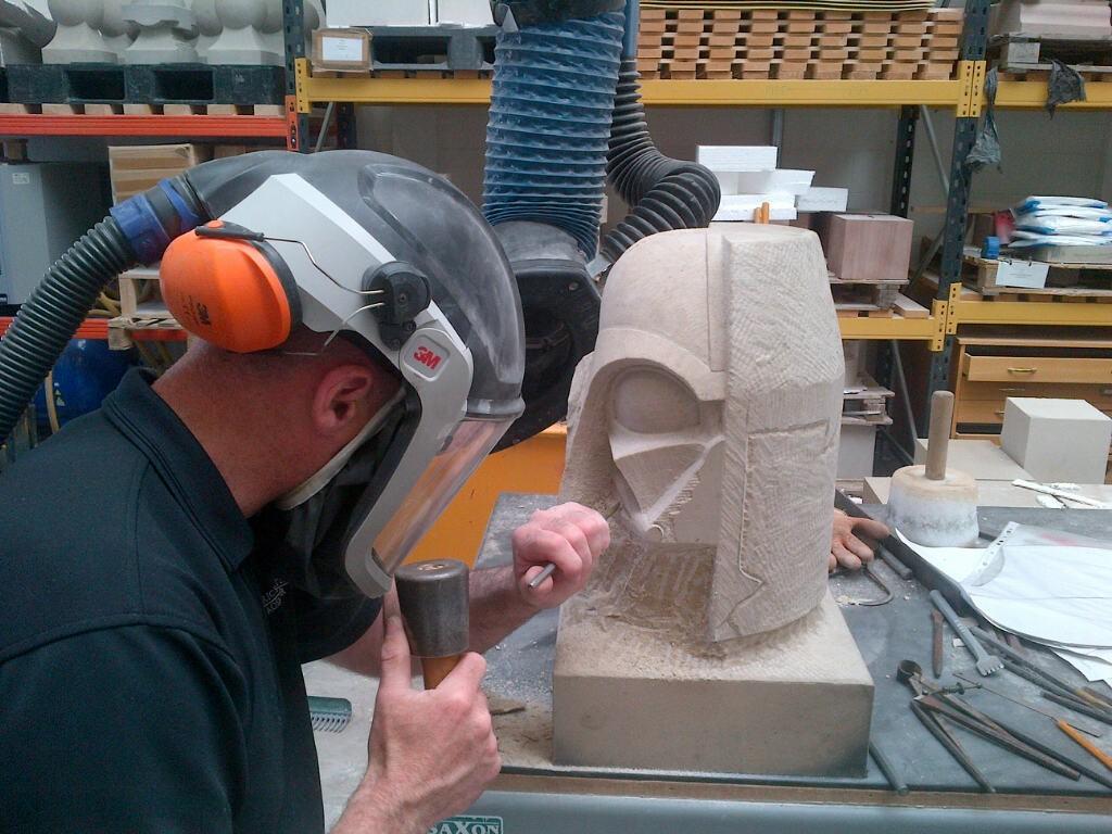 A man carving a Darth Vader grotesque