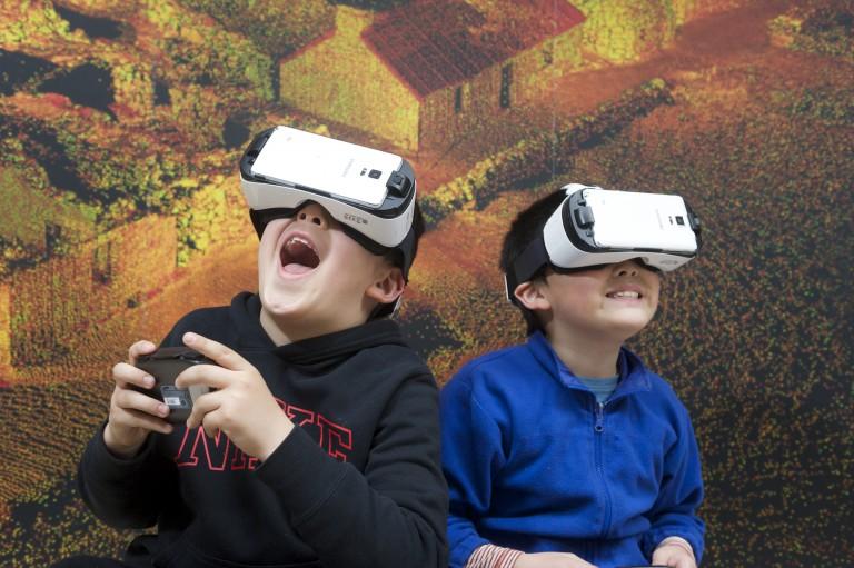 Two children using virtual reality headsets to explore a 3D digital recreation of the Antonine Wall