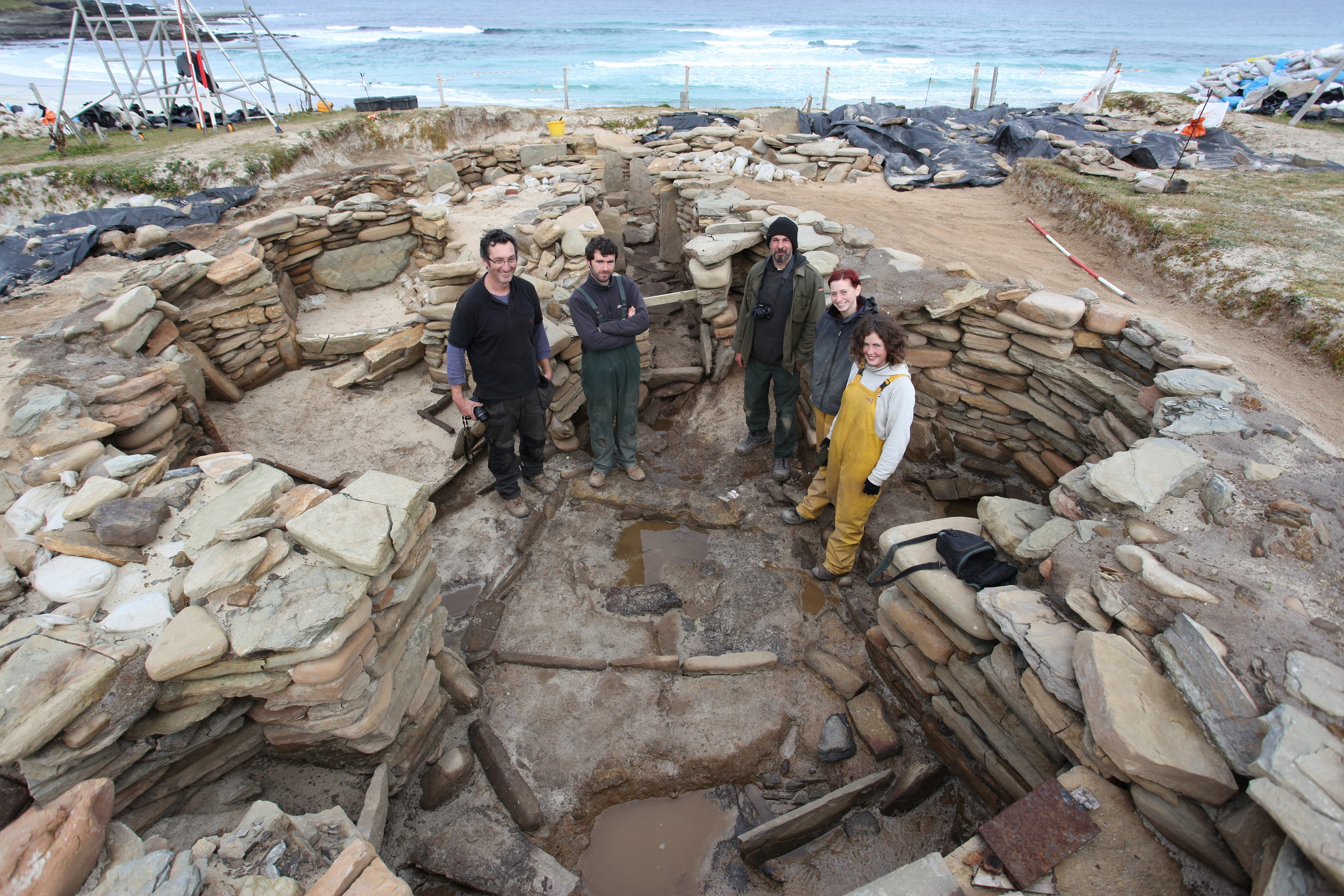 A team of archaeologists standing in an excavated building