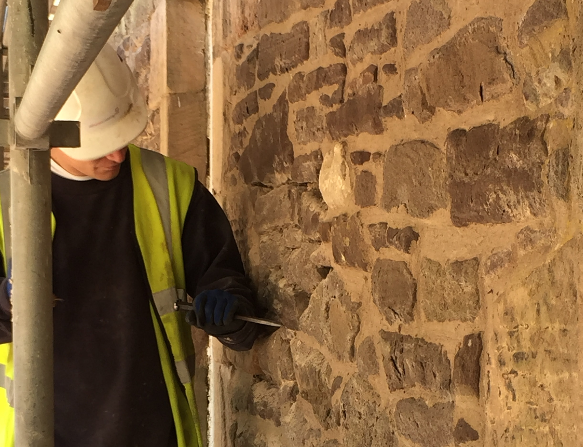 A worker inspecting a stone wall at New Lanark