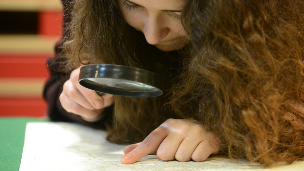 A girl with long hair uses a magnifying glass to inspect an archive document
