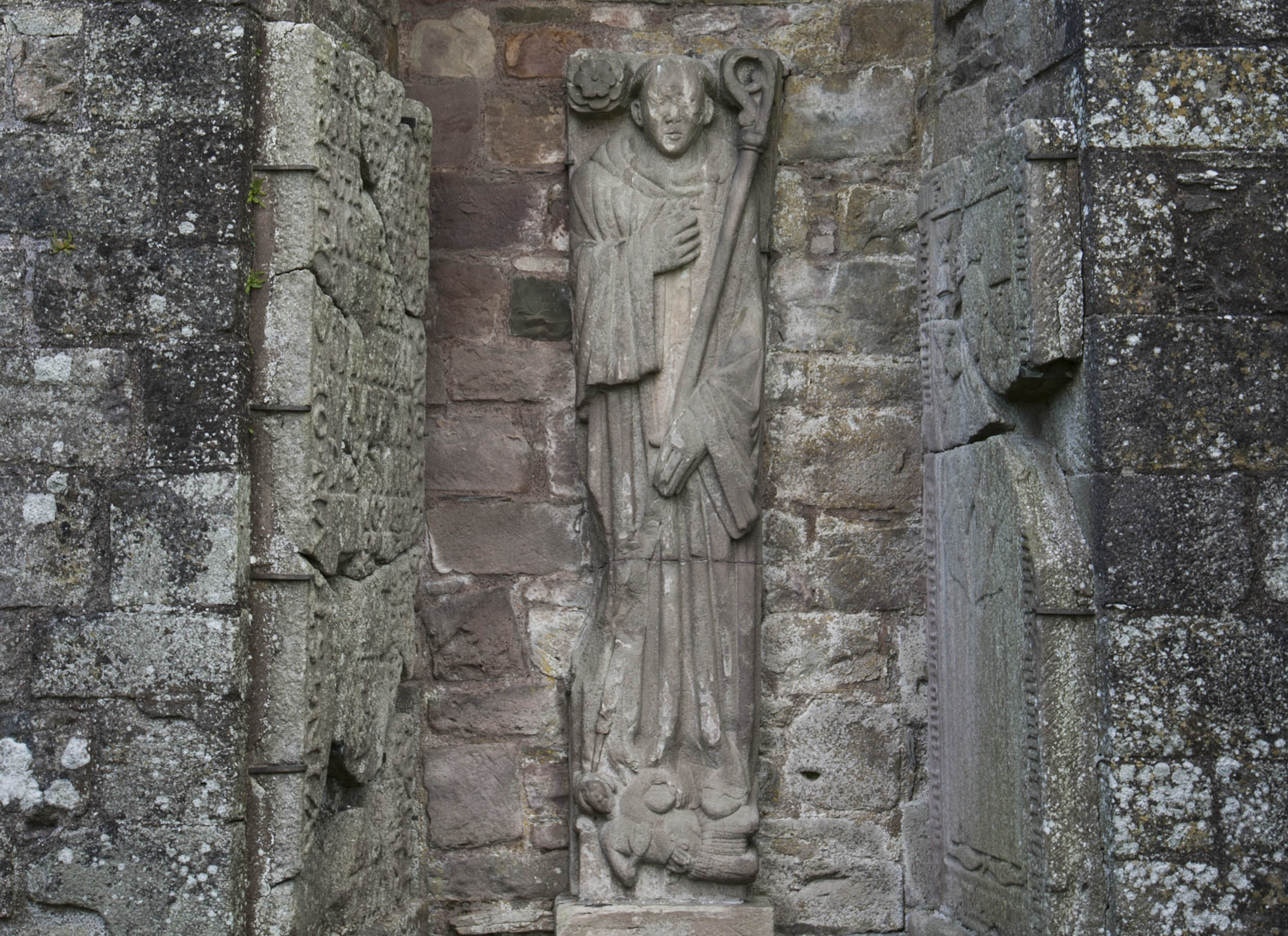 Effigy of an unknown abbot of Dundrennan. The dagger at his haert, along wih the partly disembowelled figure at his geet, has been taken to suggest that this abbot was murdered.