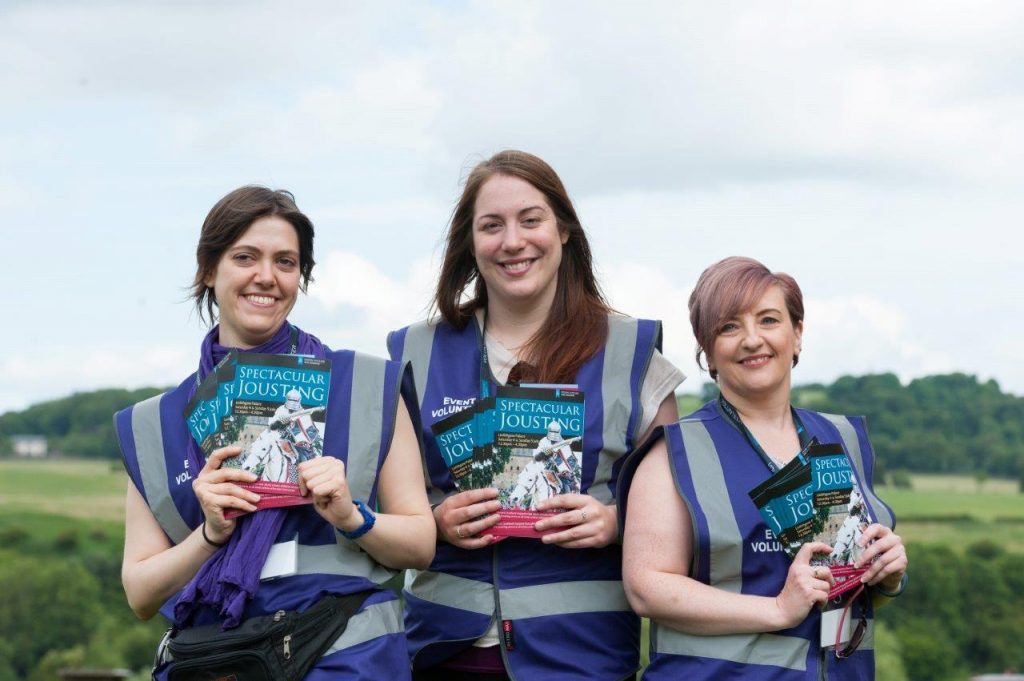 Three female volunteers holding brochures at the Spectacular Jousting event
