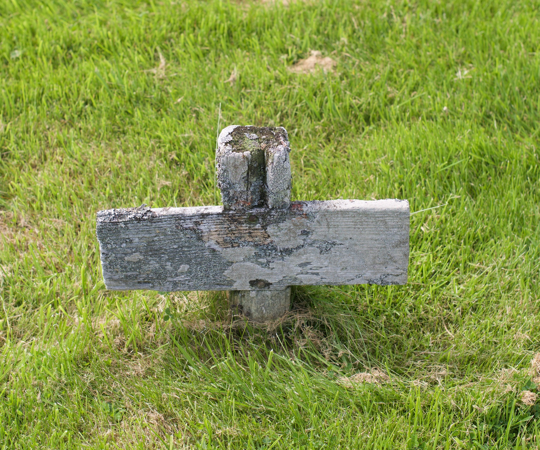 a wooden cross on grassy ground