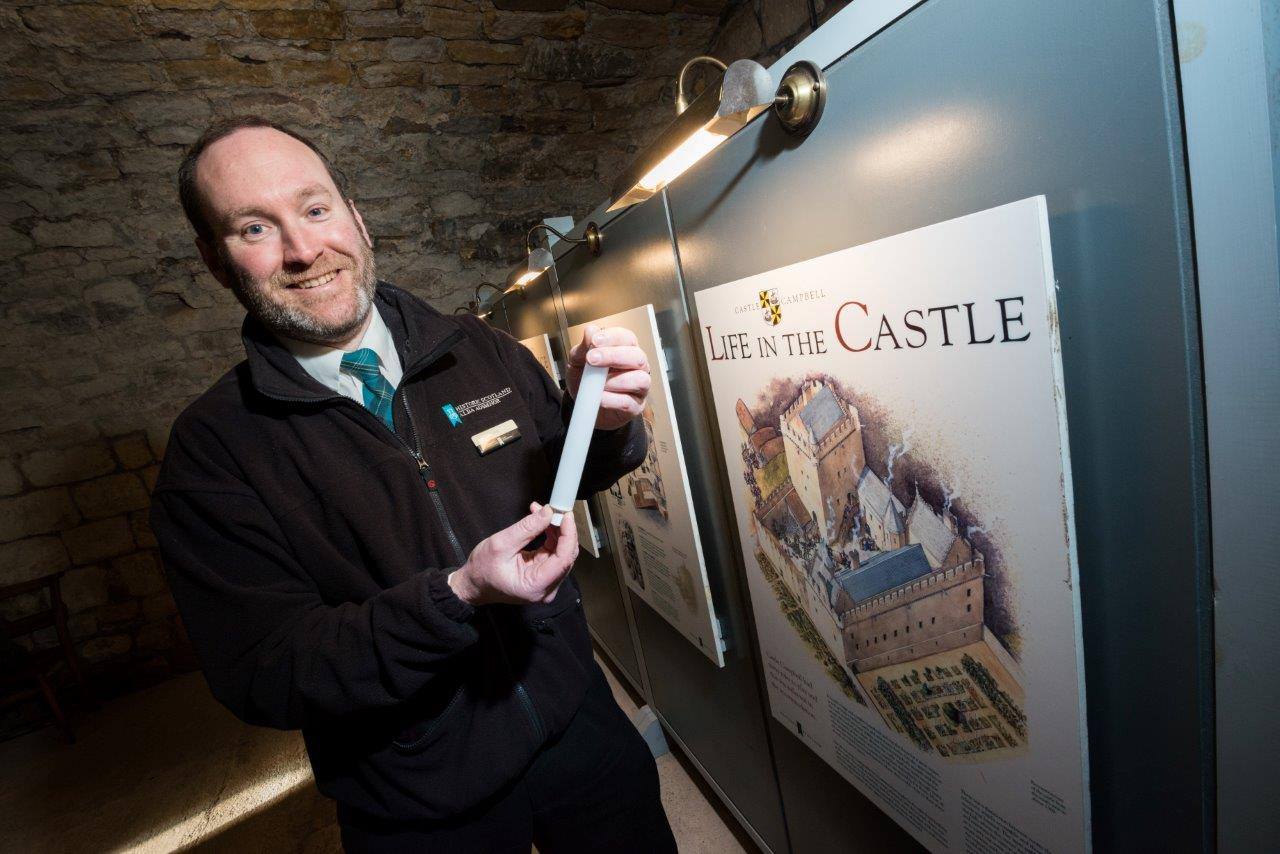 Monument manager Finlay standing in front of an interpretation display lit up with new LED bulbs