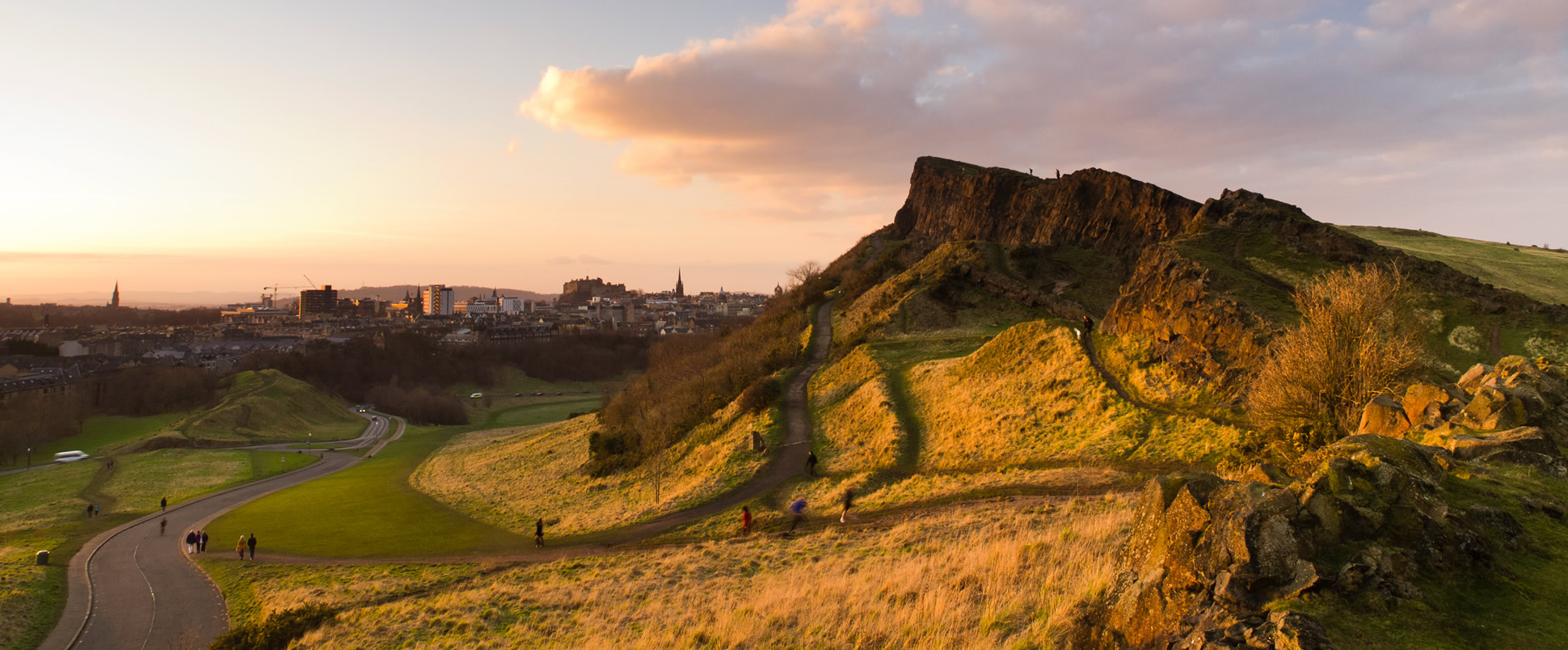 A picture of members of the public enjoying Holyrood Park at dusk.