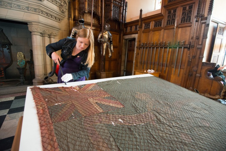 Collections Manager Rachael Dickson carries out some housekeeping work prior to the display of two colours from the Battle of Waterloo, a collaborative exhibition with The Royal Scots at Edinburgh Castle