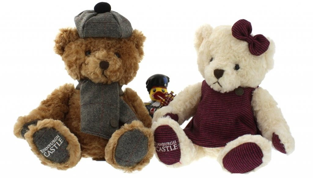 Two teddy bears with a piper duck in the middle