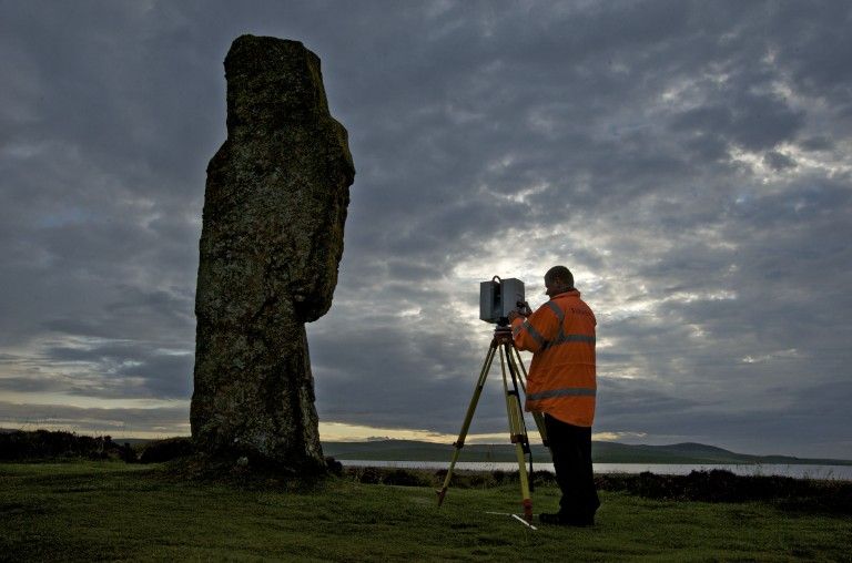 Man in orange hi-vis coat laser scanning ring of brodgar