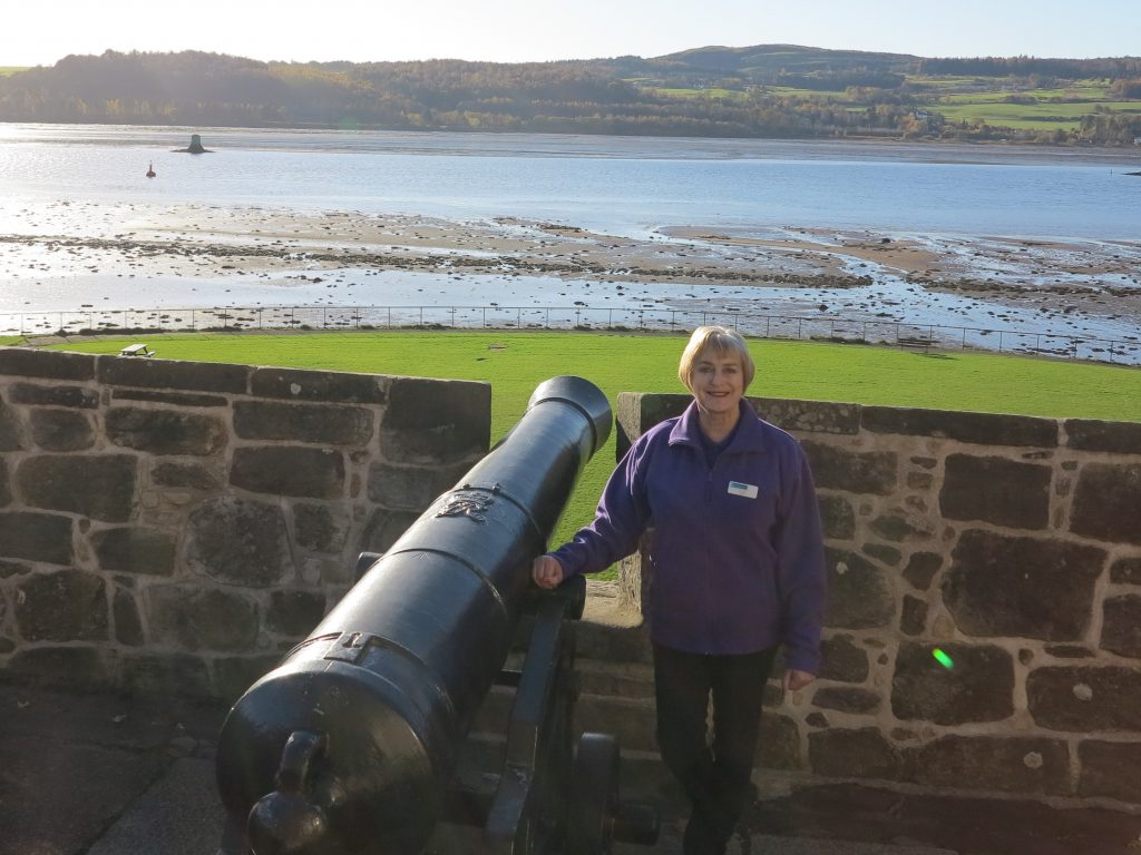 Volunteer Elspeth Crocket next to a cannon at Dumbarton Castle