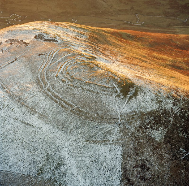 Oblique aerial view centred on the remains of Woden Law Fort