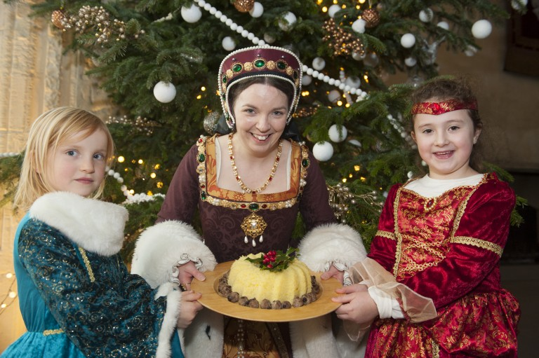 A costumed performer and two little girls show off a cake