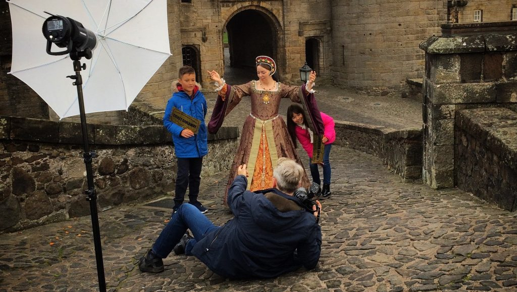 A photographer taking a picture of three models outside Stirling Castle