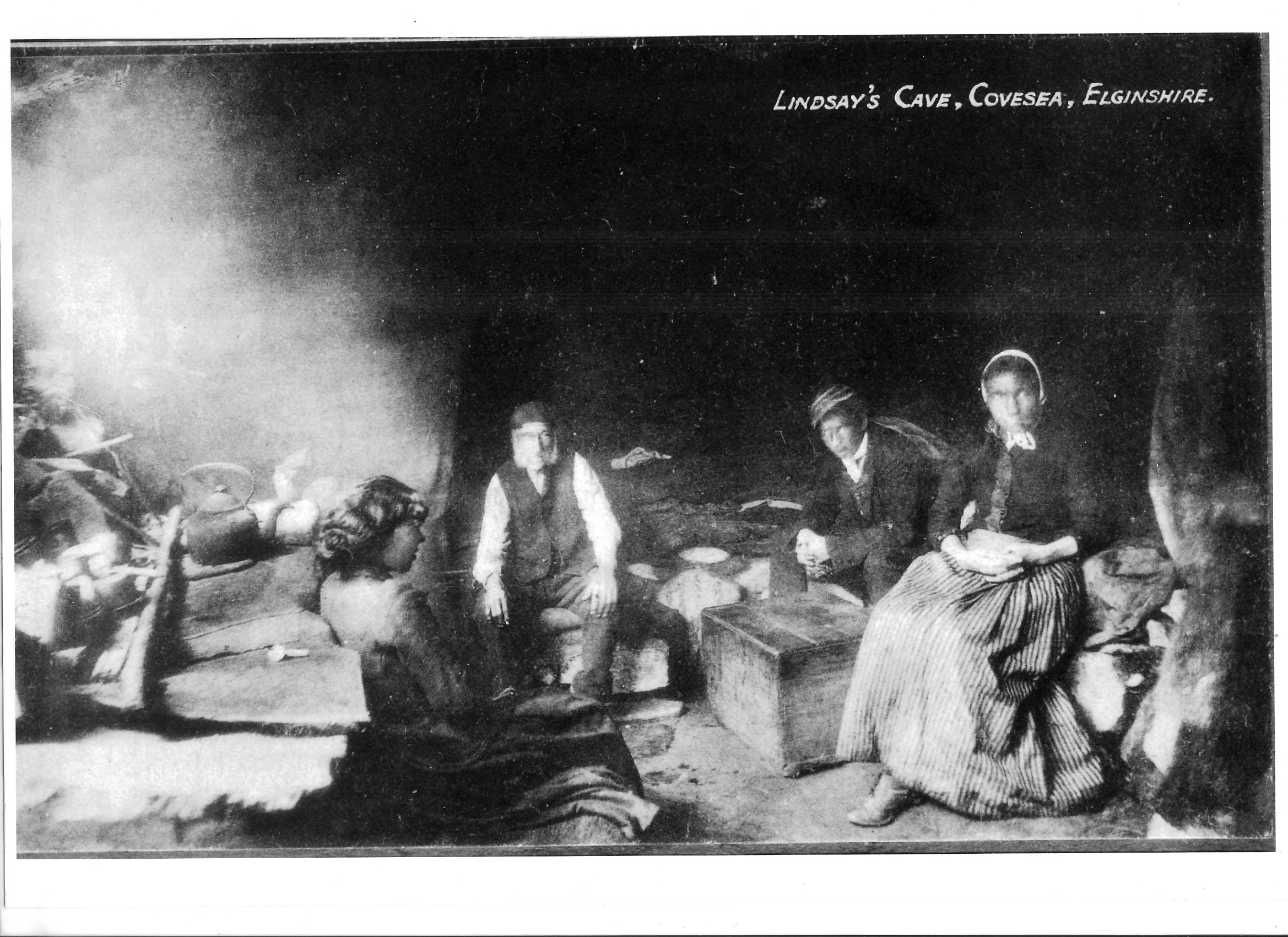 An old photograph of Travellers sitting outside a cave
