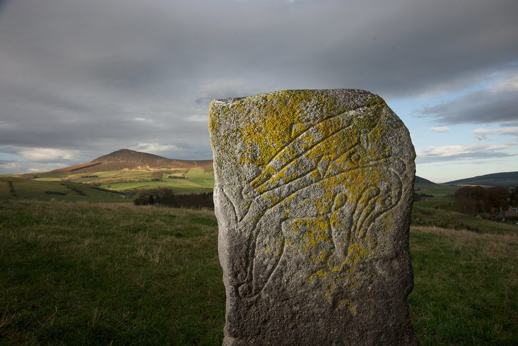 General view of the Craw Stane, standing in a field on the farm of Mains of Rhynie. This Class I Pictish stone is incised with the symbols of a fish and a Pictish beast. In the distance, behind the stone, can be seen the hillfort of Tap O North.