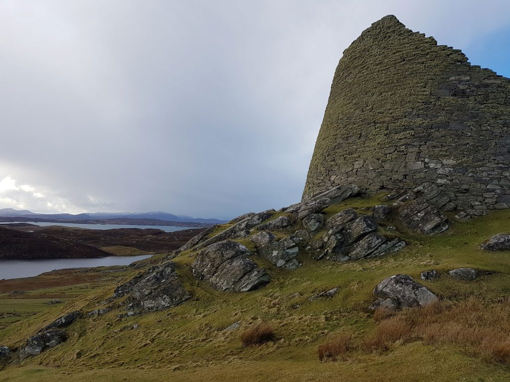 A photograph of a broch with a cloudy sky behind.