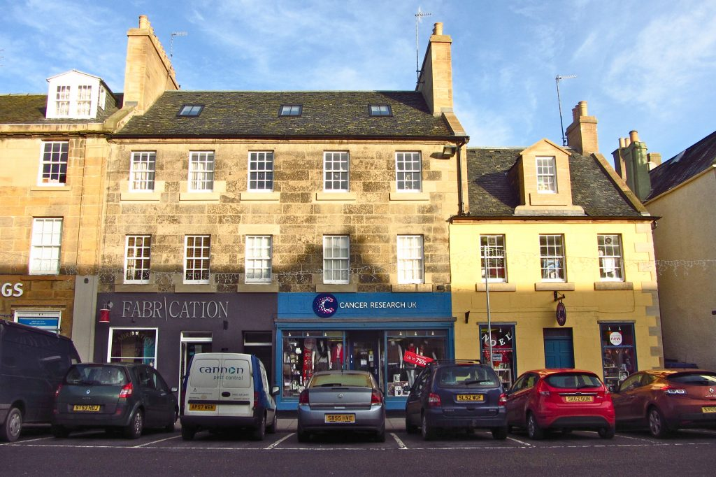 sandstone tenement building with newly painted blue Cancer Research shop front and parked cars in front