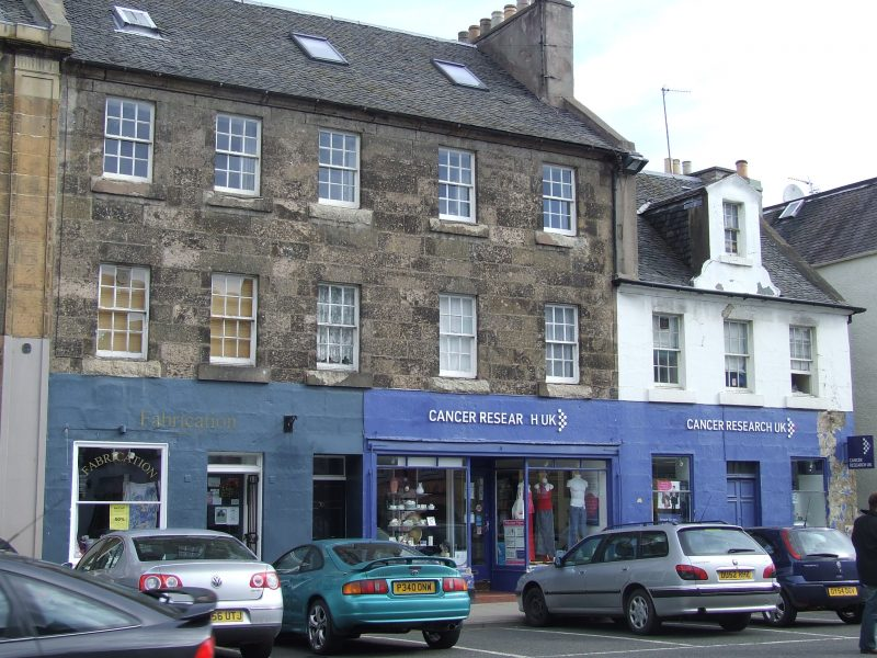 tenement building on Haddington High Street with blue shop front and cars parked outside