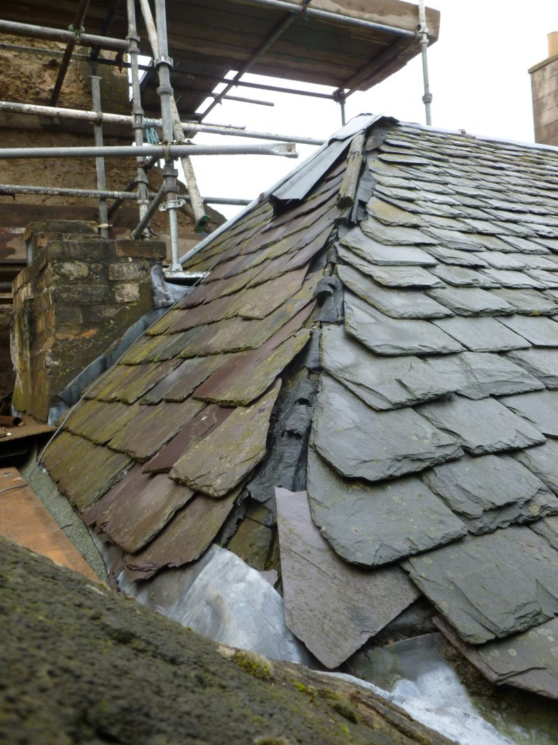 Damaged rooftop with loose tiles and scaffold