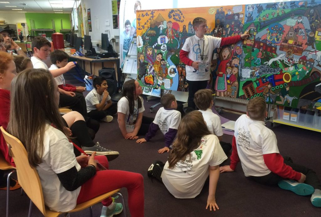 12 children seated and 1 boy standing in front of a mural of Tranent which they are discussing