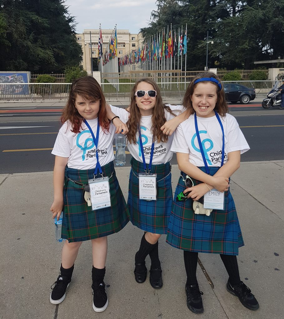 3 girls in white t-shirts and blue kilts posing outside a building with lots of flags in