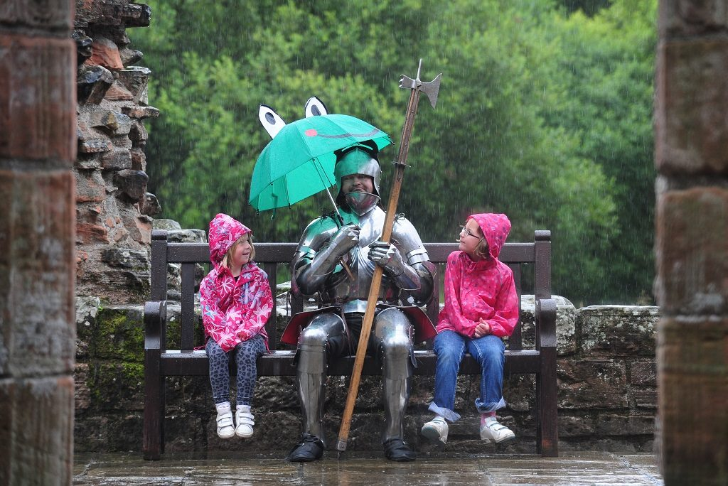 A knight with two children sitting in the rain