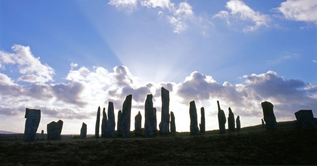 A photograph of standing stones silhouetted against the sunset.