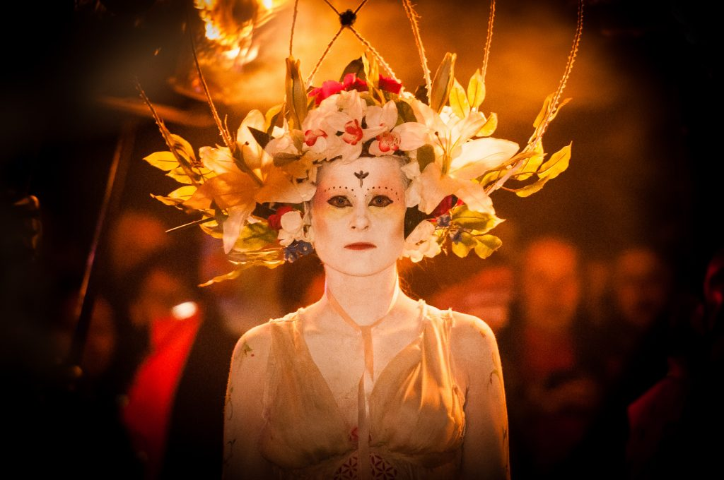 A photograph of a woman wearing white make up and a large crown made of flowers.