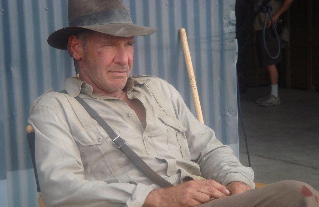 A photograph of an older man in a cream shirt and a brown hat
