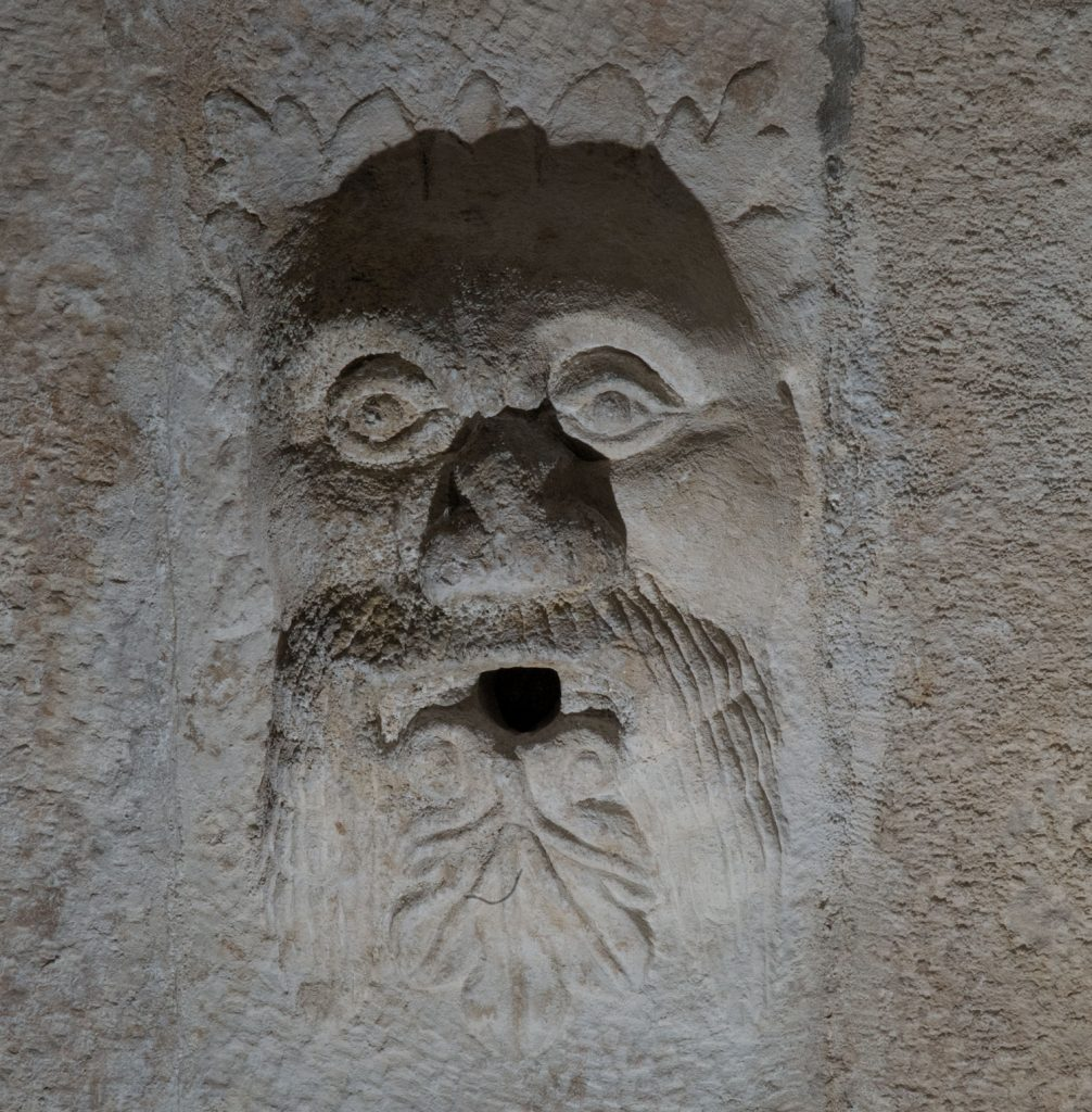 A photograph of a stone carving of a man's face with a beard