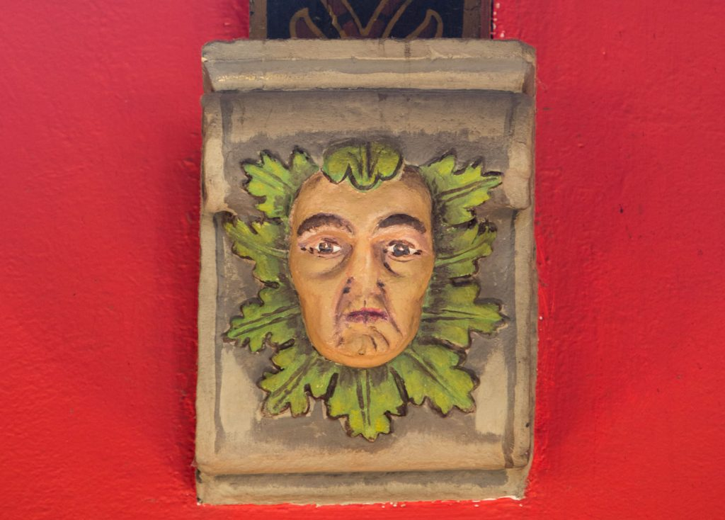 A photograph of a painted wooden carving of a man's face surrounded by leaves