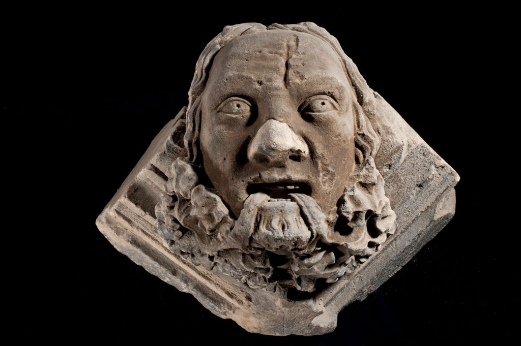 A stone carving of a man's face with thick wavy hair and foliage streaming from his mouth