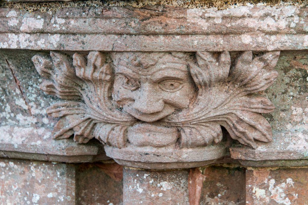 A photograph of a stone carving of a man's face eating leaves