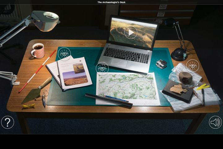 wooden desk with angle poise lamp, trowel, coffee cup, measuring stick, map, research documents, laptop and plastic bags for cataloging archaeological finds