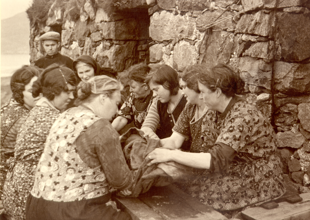 A sepia photograph of a group of women around a table with their hands on fabric.