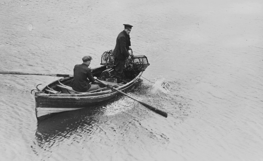 A black and white photograph of two men in a rowing boat on the water.