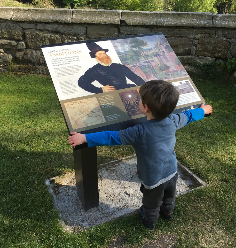 small boy with arms outstretched looks at sign with text and photo of bearded renaissance figure