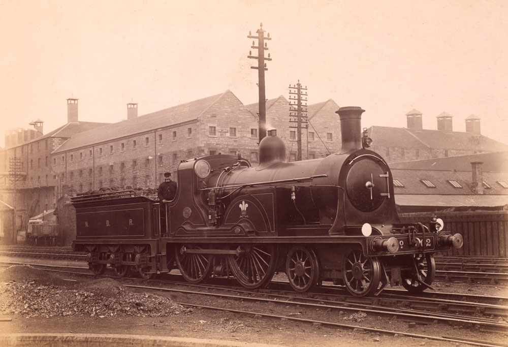 An old photograph of a steam locomotive on rails.