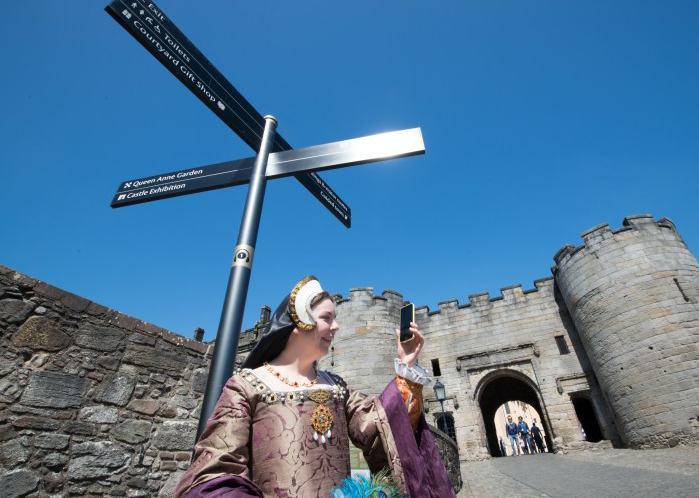 Woman wearing purple and gold corset and white and black headdress holds up a black mobile phone with a grey stone castle entrance behind her and blue sky above