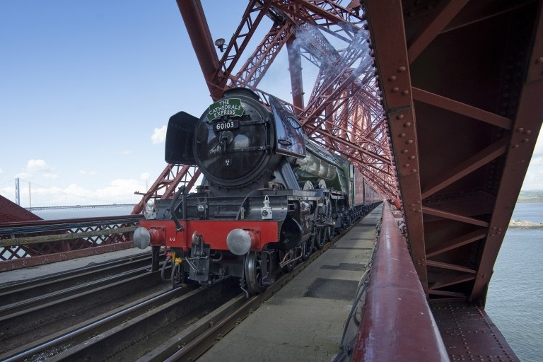 green and black steam train crossing the red painted steel Forth Bridge