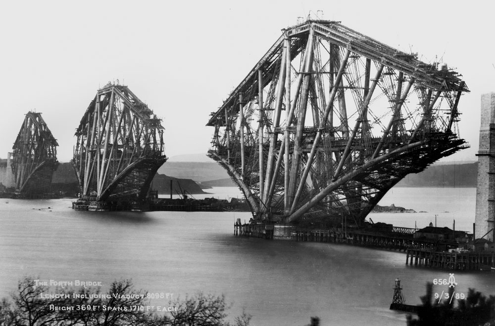 A black and white photograph of a large metal bridge under construction.