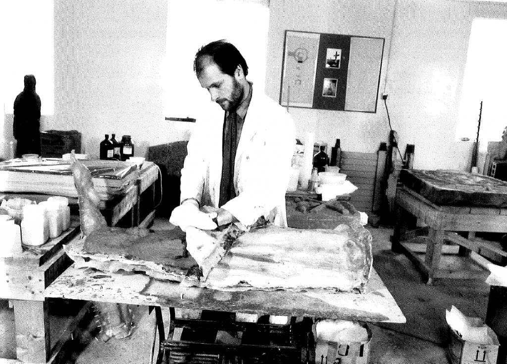 A black and white photograph of a man in a white lab coat in a conservation studio.