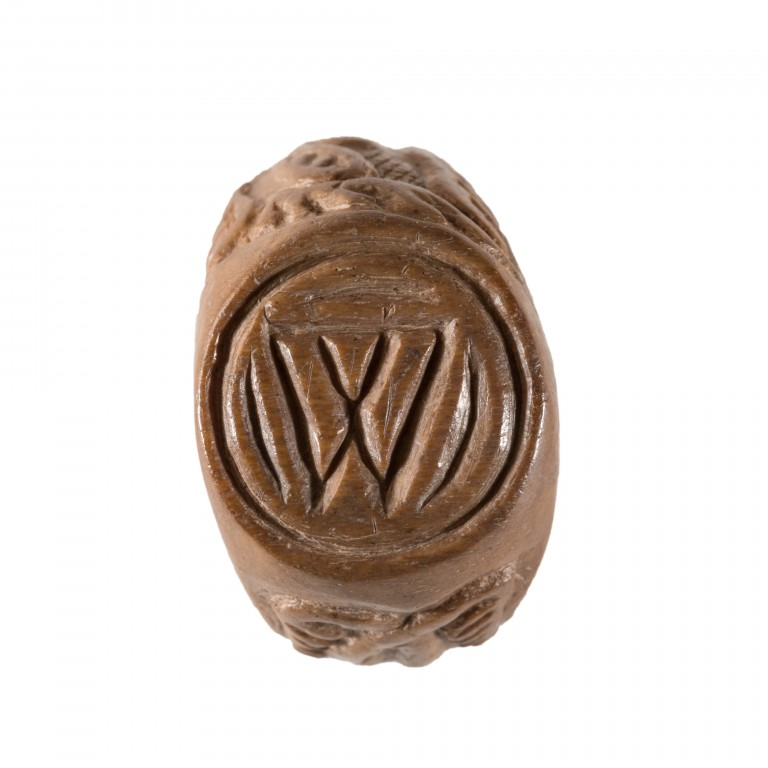 A photograph of a ring from above with a W carved into the top