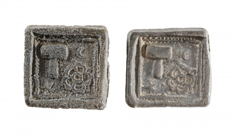 A photograph of two square artefacts with carvings on the top of a hammer and a flower